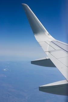 Крыло самолета на фоне голубого неба. концепция путешествия