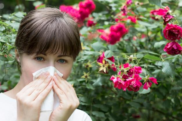開花に対するアレルギー。若い女の子がくしゃみをします。刺激