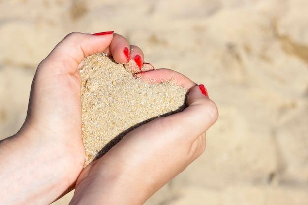 手、夏、愛、休暇の概念の砂のハート