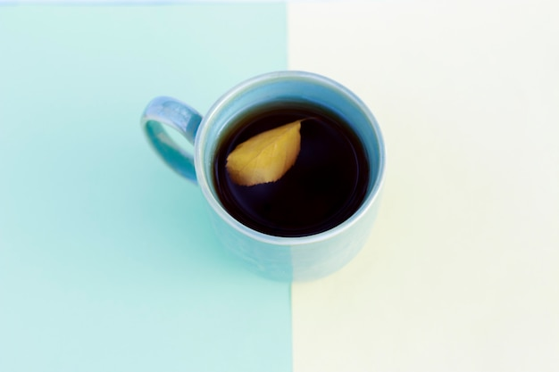 秋の色とりどりの黄色と青の紙とコーヒーのカップ