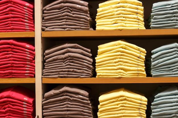 Груды разноцветной одежды на полках в магазине
