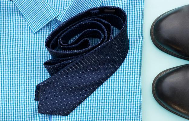 Набор одежды и аксессуаров для человека на синем фоне, бизнес или концепция офиса