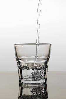 Вода наливается в стакан на светлом фоне, крупный план