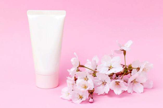ピンクの背景、正面、化粧品ケアの概念上のクリームとチューブ