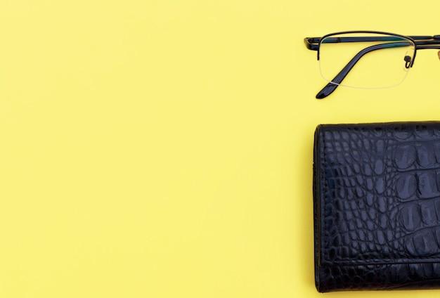 黒の財布と黄色の背景、コピースペース、ビジネスまたはオフィスコンセプトにメガネ