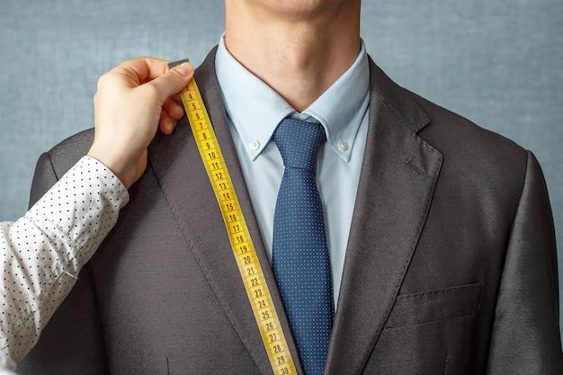 仕立て屋は測定テープのクローズアップでスーツを測定します