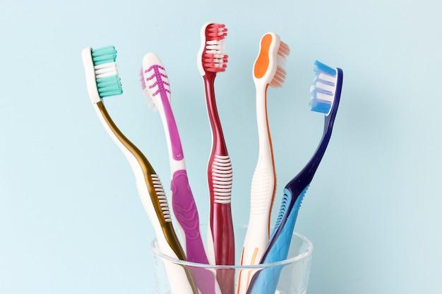 ガラスカップの正面図で色とりどりの歯ブラシ