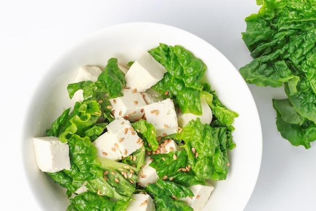 グリーンサラダと豆腐のスライス、白い壁、トップビューでボウルします。