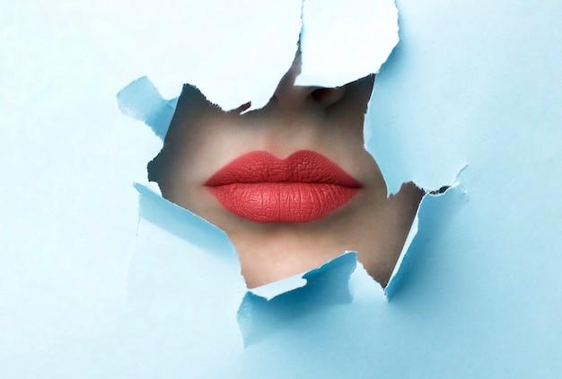 赤い唇と青い引き裂かれた紙の背景