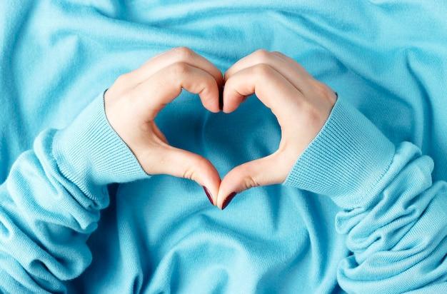 Женские руки с маникюром в форме сердца на синем фоне