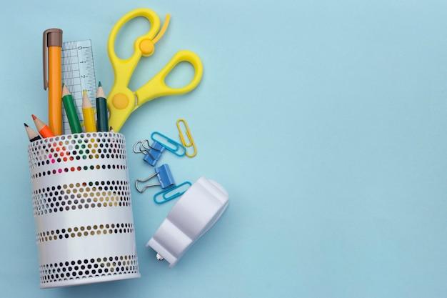 柔らかい青い背景上の学校のアクセサリー。学校のコンセプトに戻る子供のための創造性カラフルな学校の背景。コピースペース