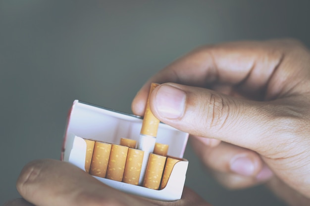 男の手持ち株を閉じるそれをタバコのパックからはがすそれはタバコを吸う準備をします。