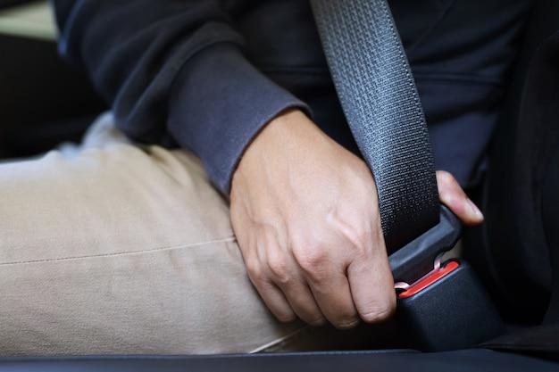 道路を走行する前に安全のために車のシートの安全ベルトを締める人の手のクローズアップ