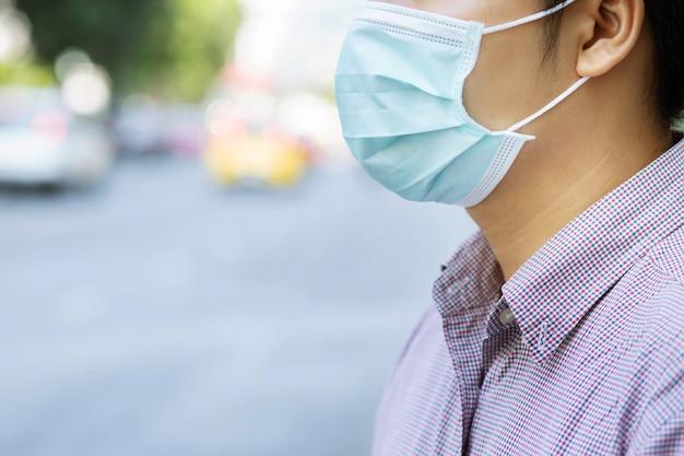 屋外の顔の衛生マスクの鼻を着た男の肖像。