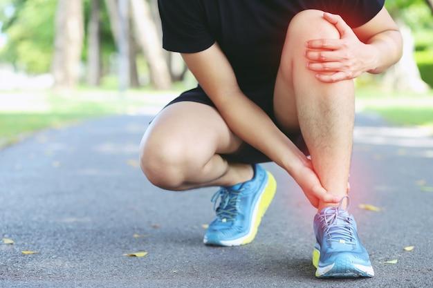 Бегун прикасается к болезненной скрученной или сломанной лодыжке. тренировка спортсмена бегуна.