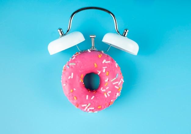 Пончики глазируют с будильником на синем. пончики будильник.