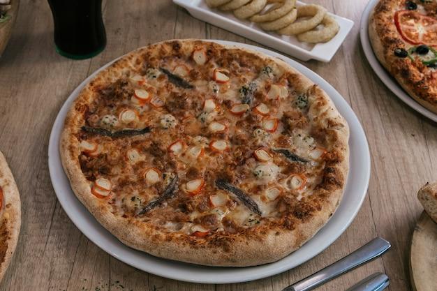 Вкусная пицца из морепродуктов на белой тарелке на деревянном фоне