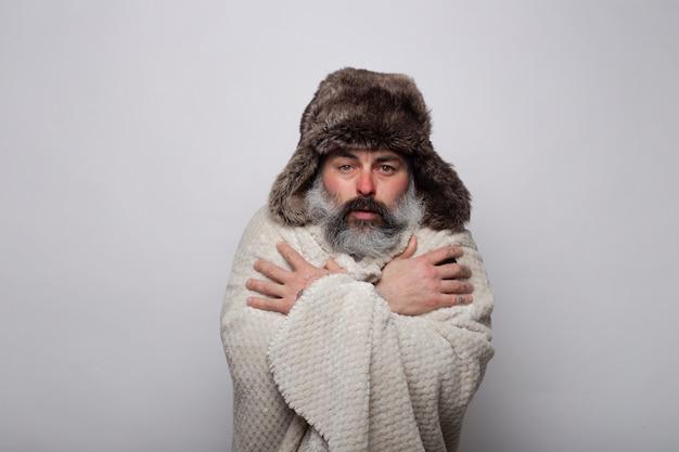 寒さで揺れる毛布と帽子で身を覆う中年の男性