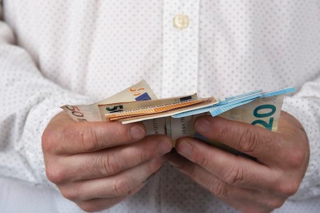 お金を持つ男。現金紙幣のユーロの金額