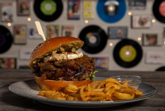 Домашний говяжий бургер с козьим сыром, карамелизированным луком и картофелем фри. изолированное изображение