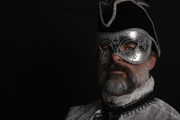 マスク、帽子、ベネチアンシャツ、黒い背景にひげを持つ男。カーニバルのコンセプト