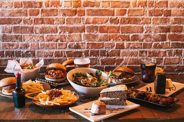 Разнообразие блюд ресторанного меню. салат с козьим сыром, домашние гамбургеры и картофель фри, напиток, куриные крылышки, овощная темпура и пирожные на деревянном столе.
