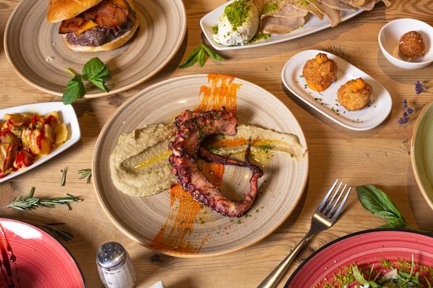 さまざまな肉や魚の食事の分離イメージ。さまざまな料理のビュッフェの上面図。ビュッフェ、宴会、前菜、レストランメニューのコンセプト。