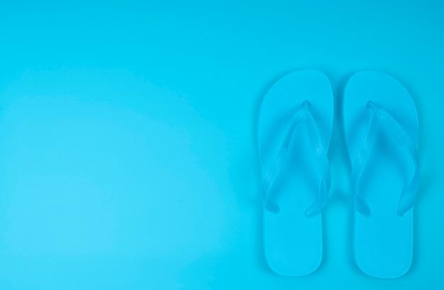 ビーチには青のビーチサンダルがあります。夏がコンセプトです。