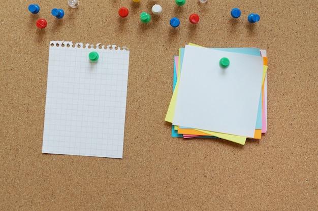 コルク板に空白の臭いメモピン。空白のメモとコルクボード。