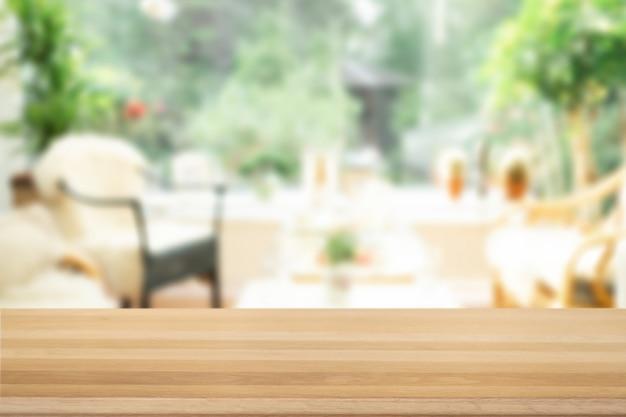 背景をぼかした写真の前に茶色の空の木製テーブルトップ。リビングルームのインテリアにぼやけた光の木。