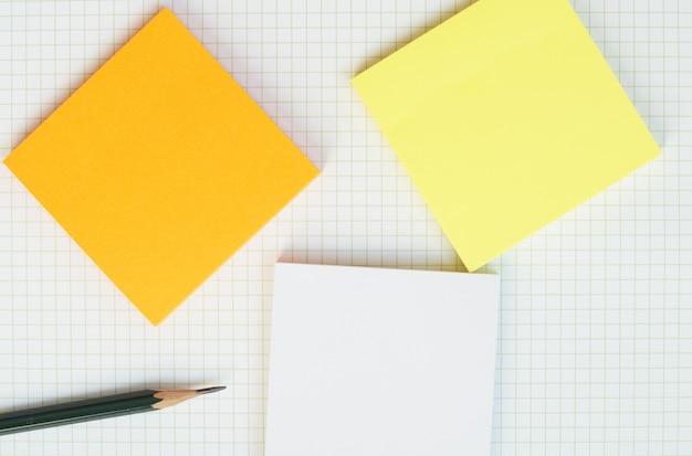 緑の木製鉛筆と空白のグリッド紙に付箋紙。