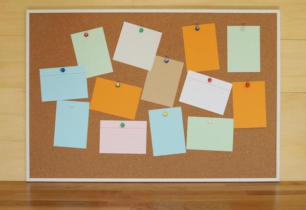 木製のテーブルの床に背景紙カードの抽象的なコルク板テクスチャ上の空白の紙メモピン