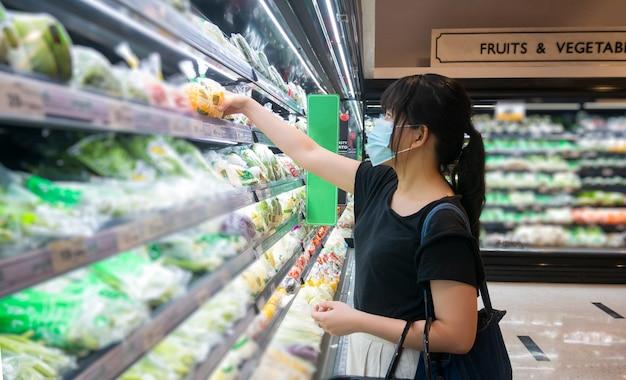 アジアの女性は食料品店で買い物をし、バスケットを持って、健康マスクを着用しています