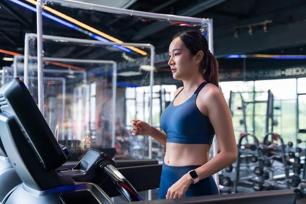 Женщины бегут по беговой дорожке в спортзале.