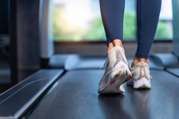 クローズアップ女性の足がジムでトレッドミルで実行されています。女性はストレッチし、スポーツと健康の概念で有酸素運動の前にウォーミングアップします。