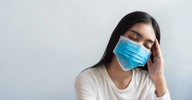 アジアの女性は頭痛のためにマスクをして頭を抱えています。彼女は、ストレスや睡眠不足、睡眠不足、コピースペースのある健康的なコンセプトでは不十分な休息のために、発熱と片頭痛を抱えています。