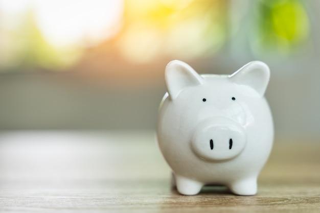 お金の節約の概念日光のボケ味を持つ木製のテーブルにお金を節約の貯金箱のシンボルは、壁とコピースペースをぼかします。