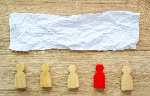 Мятую бумагу и красную фигуру среди деревянных фигур