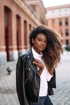 Портрет привлекательной молодой женщины в черной кожаной куртке, глядя на камеру.