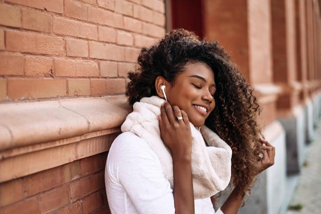 ヘッドフォンで音楽を聴く都市の背景に魅力的な黒人少女の肖像画。