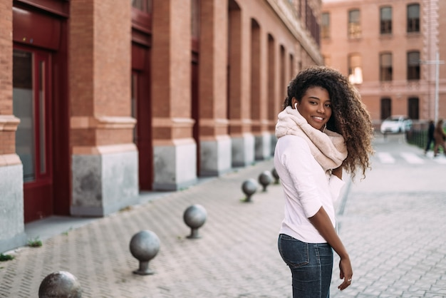Портрет веселый молодой леди на улице города, слушать музыку с наушниками.