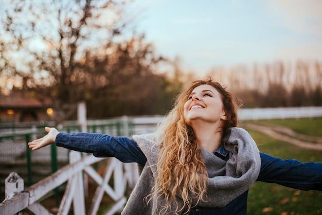 Свободу чувствую хорошо. радостная женщина поднимая руки снаружи.