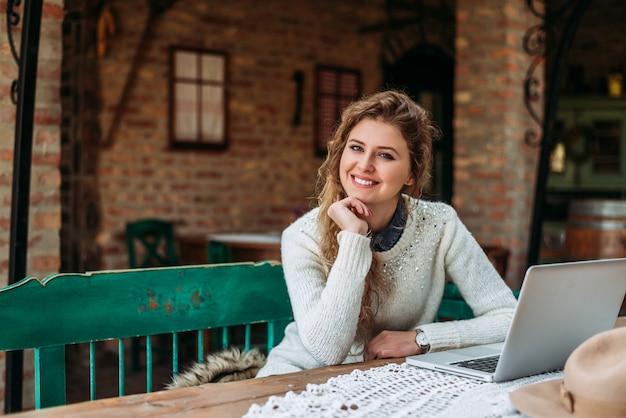 外に座っているとラップトップを使用して美しい金髪の女性の肖像画。