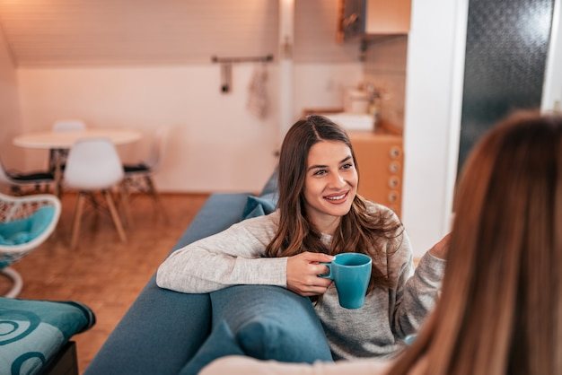 自宅で女性の友達がお茶を飲みます。