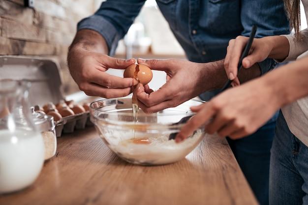 Конец-вверх пар варя и ломая яичка в шар в кухне дома.