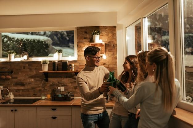 Друзья, приветствующие дома вечеринку. зимние каникулы и люди концепции.