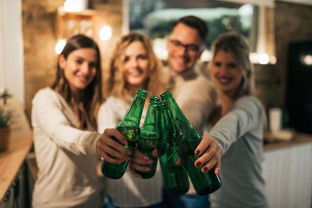 友達がボトルで乾杯し、前景に焦点を当てます。