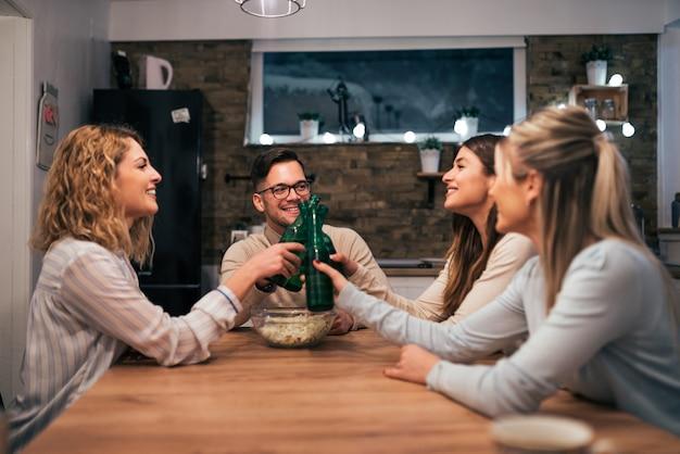 Друзья сидят за столом дома, аплодируют бутылками с напитком.