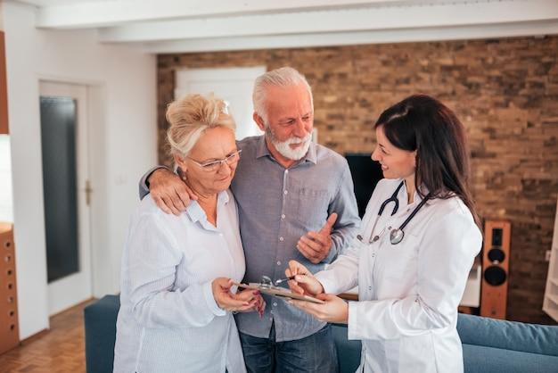 年配のカップルが家庭訪問で女医と話しています。