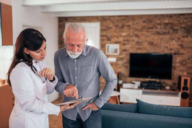 医師が訪問中に高齢の患者に健康診断の結果を示す。